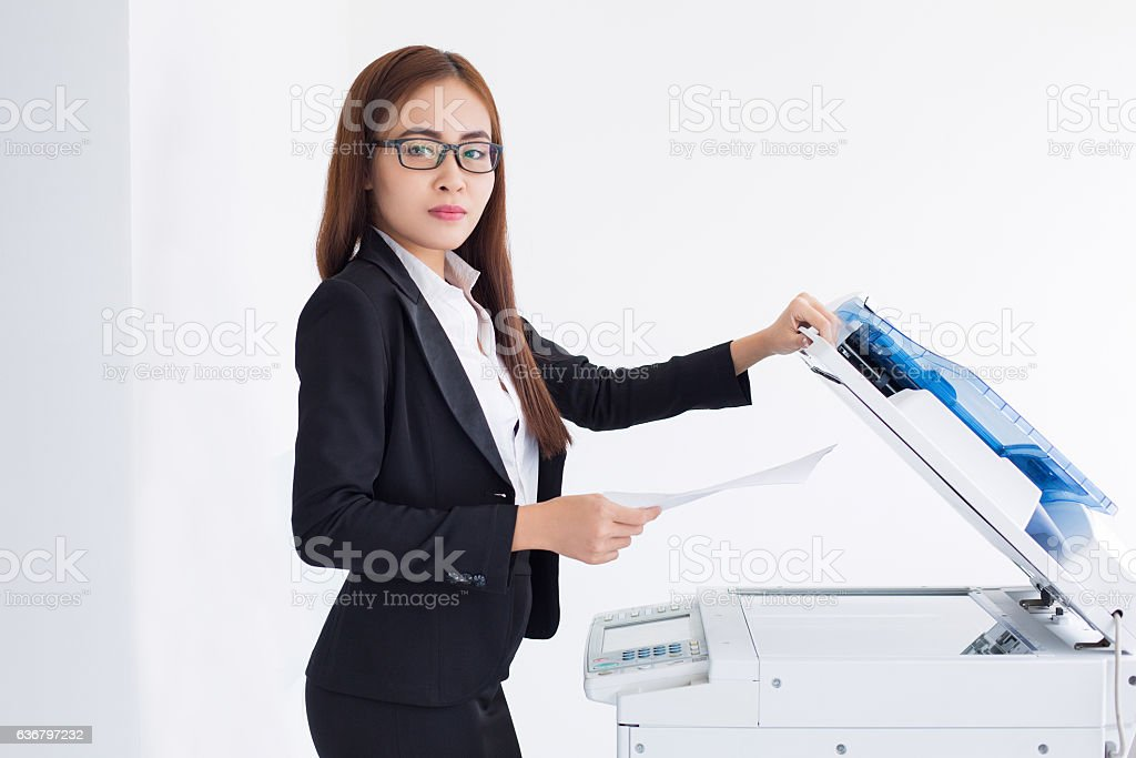 Content Asian Female Assistant Using Photocopier stock photo