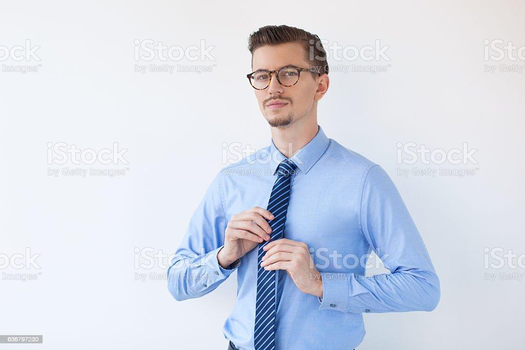 Content Elegant Male Manager Adjusting Tie stock photo