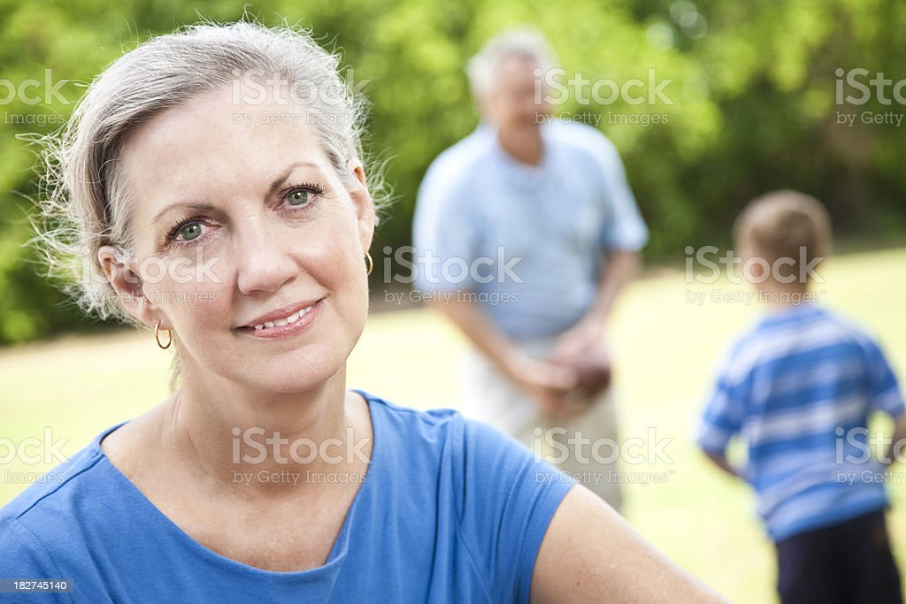Content Grandmother in front of Husband and Grandson Playing Football royalty-free stock photo