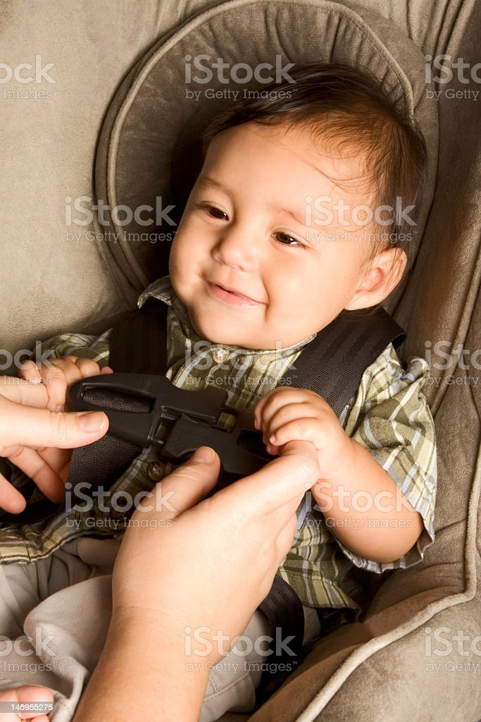Content infant boy being buckled into his caraway stock photo