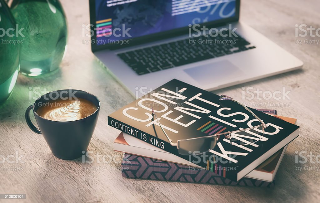 content is king, coffee and books with computer stock photo