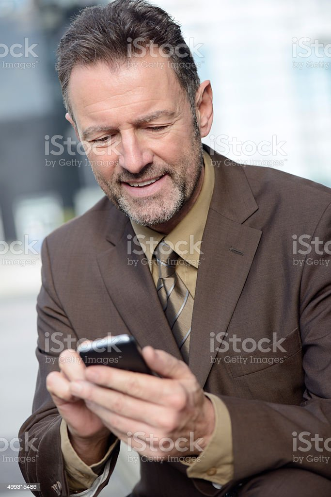 Content mature businessman typing on his smartphone stock photo