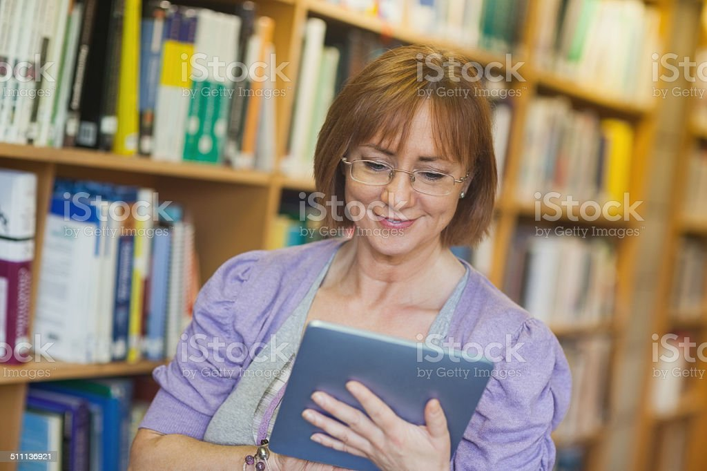 Content mature librarian using her tablet stock photo