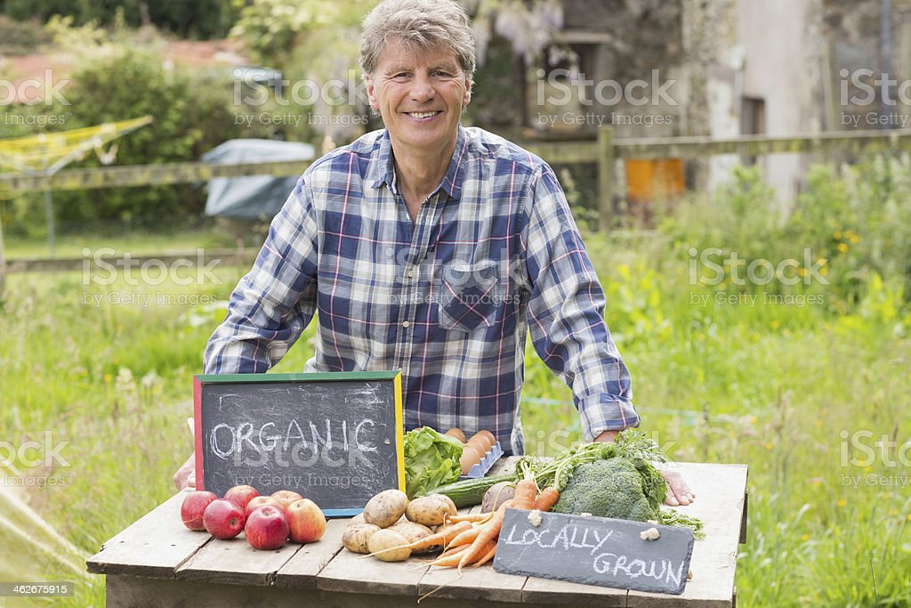 Content mature man presenting his vegetables royalty-free stock photo