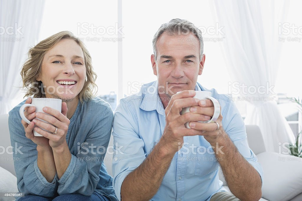 Content middle aged couple sitting on the couch having coffee stock photo