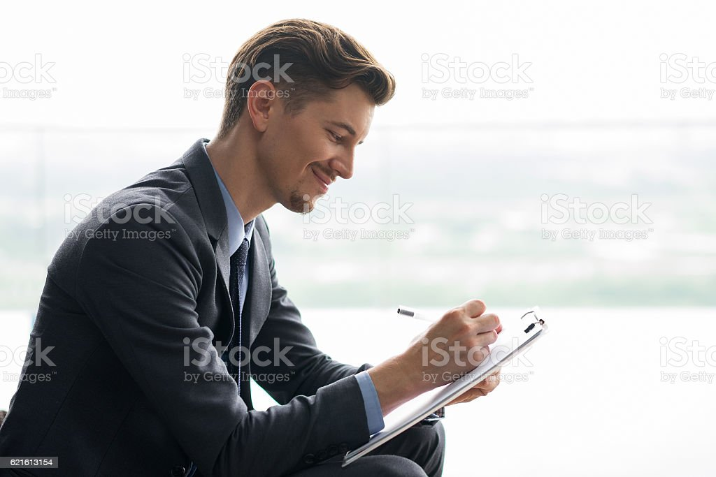 Content Middle-aged Businessman Making Notes stock photo
