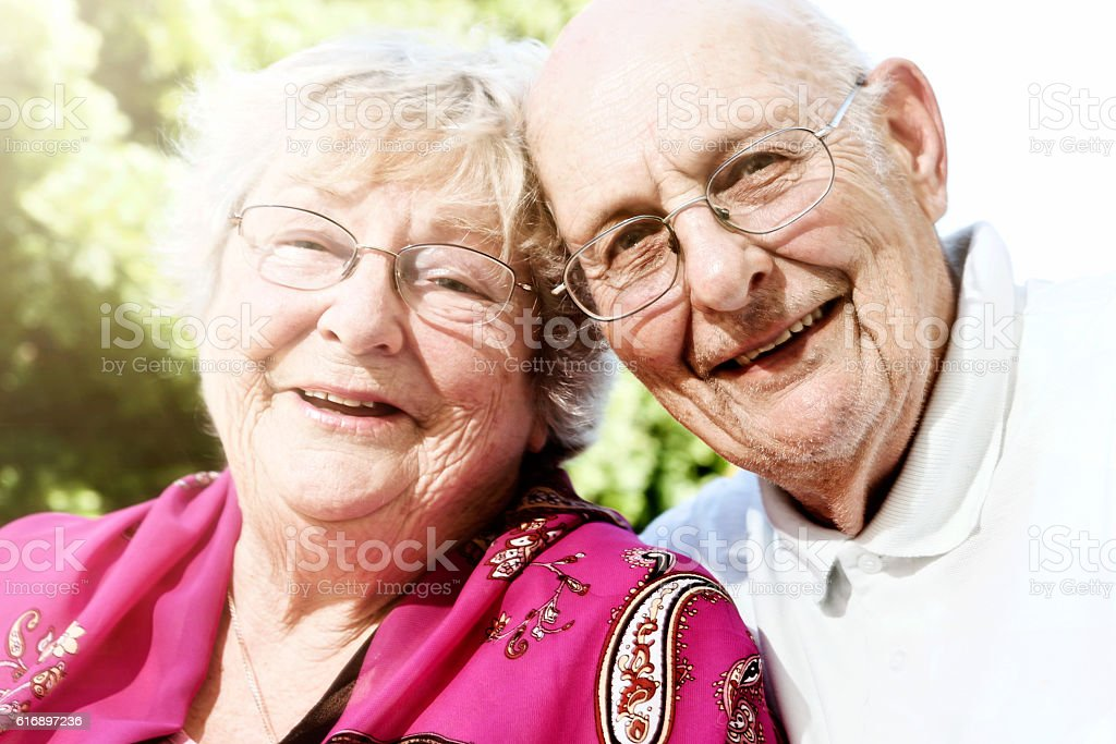 Contented couple in their 80s smile in their sunny garden stock photo