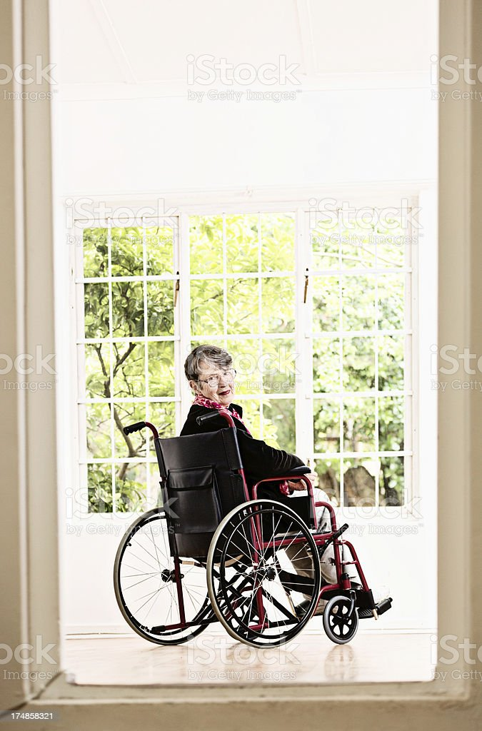 Contented old woman in wheelchair looks over her shoulder, smiling royalty-free stock photo