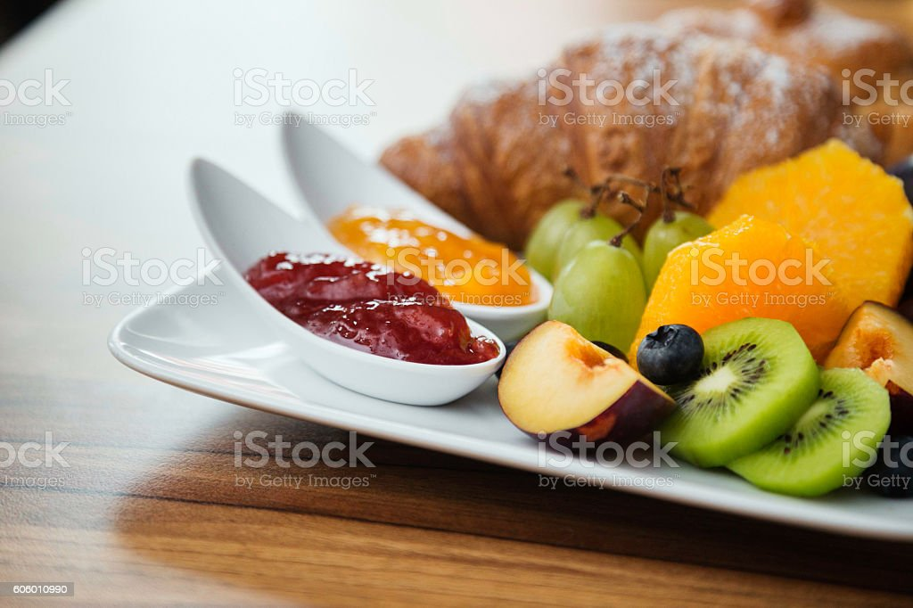 Continental breakfast with fresh fruit, jam and croissant. stock photo