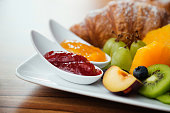 Continental breakfast with fresh fruit, jam and croissant.