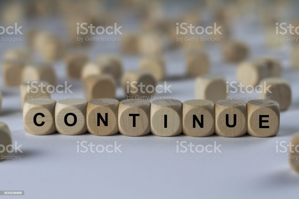 continue - cube with letters, sign with wooden cubes stock photo