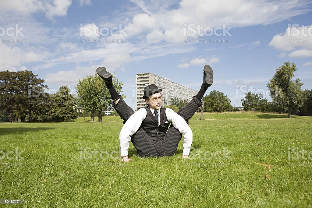 Contortionist sitting in a field stock photo