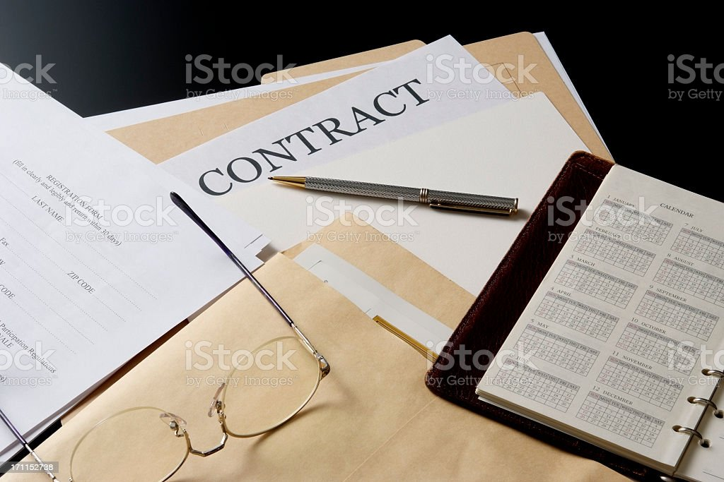 Contract documents and personal organizer on the office desk royalty-free stock photo