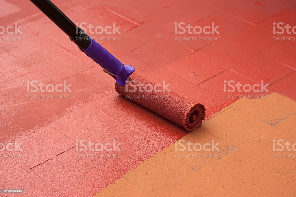 Contract painter painting a floor on color red stock photo