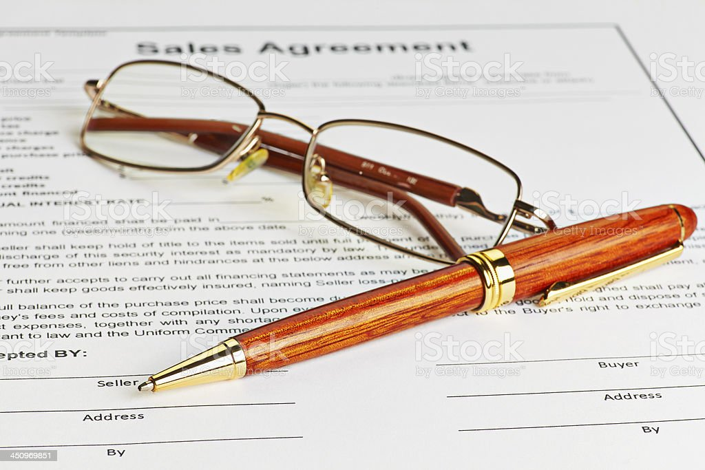 Contract with glasses and wooden pen ready to be signed stock photo