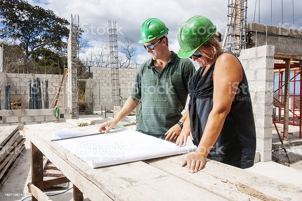 Contractor and architect checking construction progress royalty-free stock photo