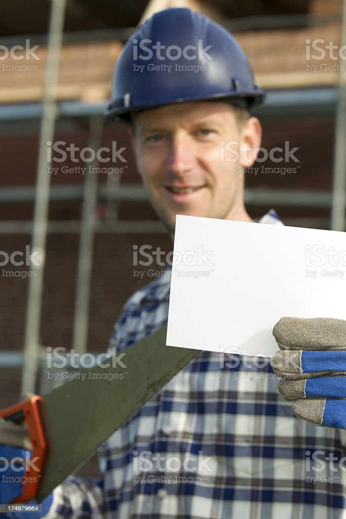 Contractor by construction pointing at piece of paper royalty-free stock photo