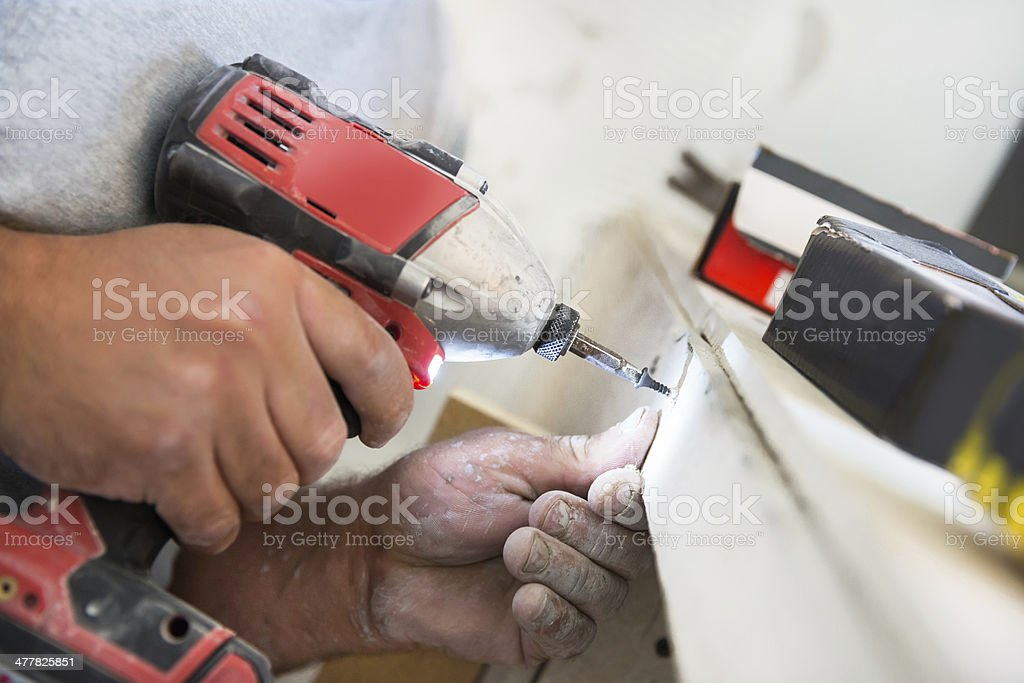 Contractor drills screw into wood royalty-free stock photo