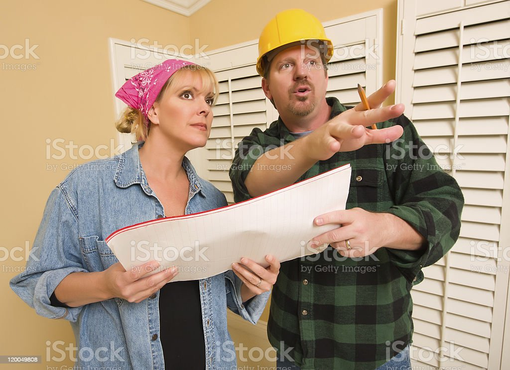 Contractor in Hardhat Discussing Plans with Woman royalty-free stock photo