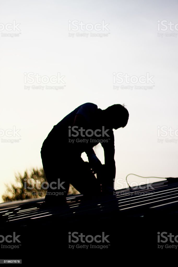 Contractor in Silhouette working on a Roof stock photo