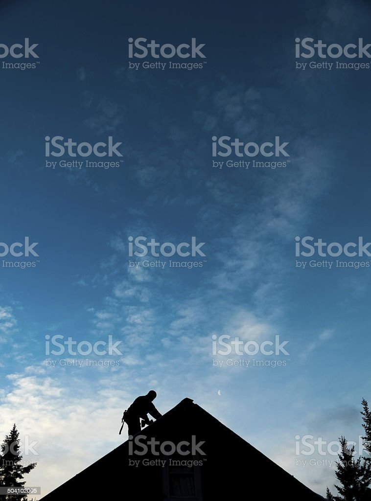 Contractor in Silhouette working on a Roof Top stock photo
