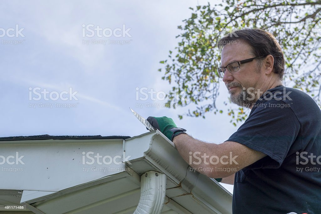 Contractor Installing Plastic Gutter Guards stock photo