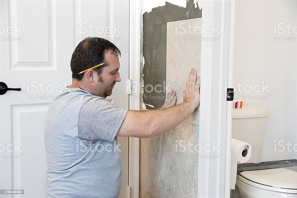 Contractor installing tile on a bathroom wall royalty-free stock photo