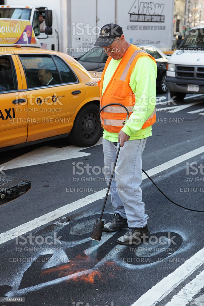 NYC contractor places bicycle symbols on Sixth Avenue royalty-free stock photo