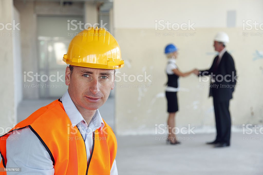 Contractor with handshake in the back royalty-free stock photo