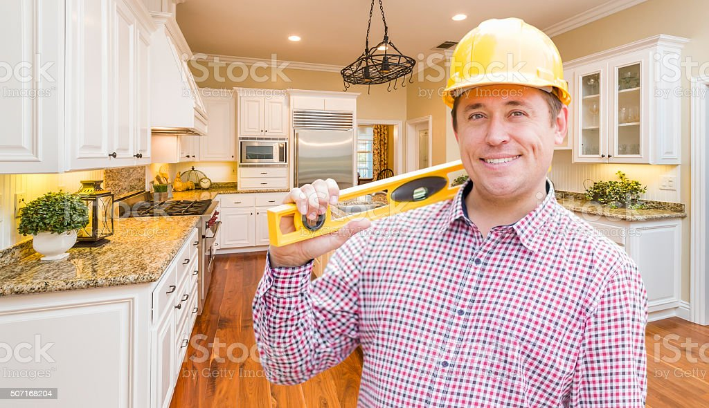 Contractor with Level Wearing Hard Hat Standing In Custom Kitche stock photo