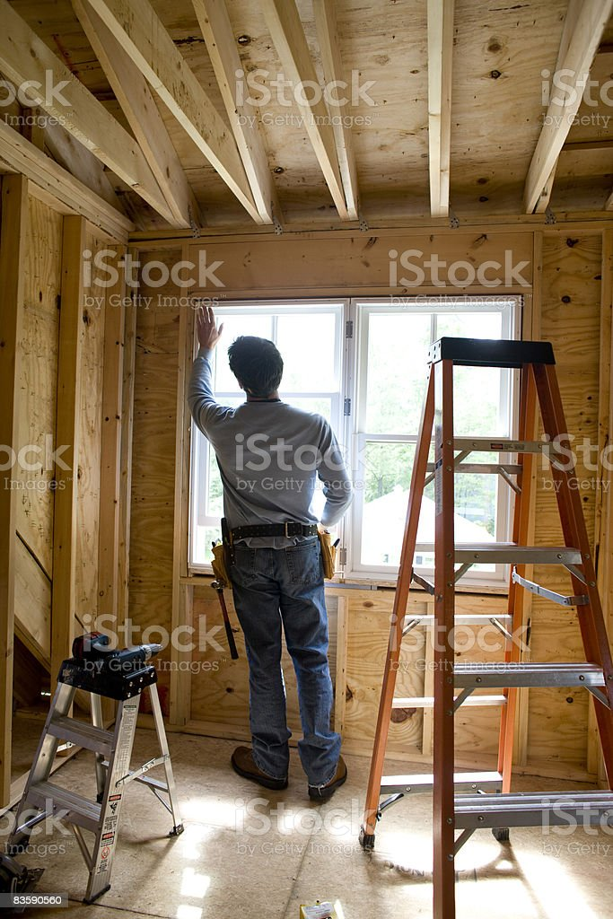 Contractor working on window in new home stock photo