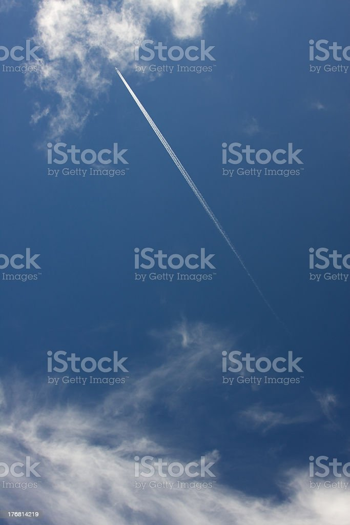 Contrail against blue sky royalty-free stock photo