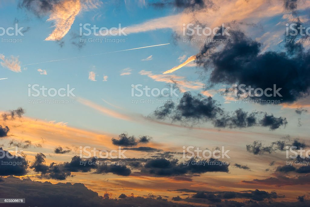 Contrail in blue sky with clouds at sunset stock photo