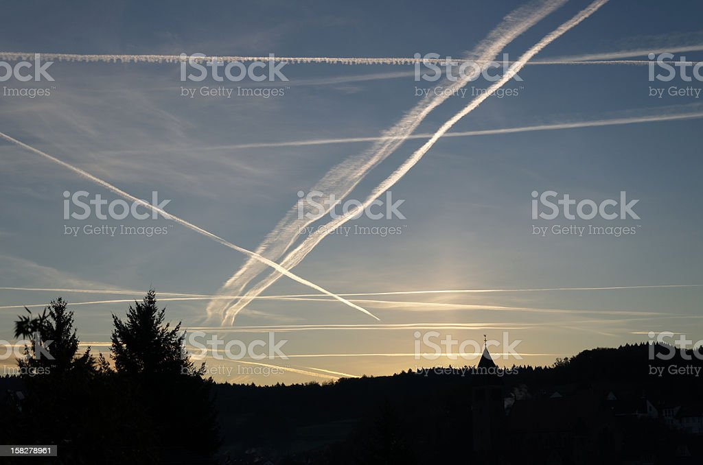 contrails above village royalty-free stock photo