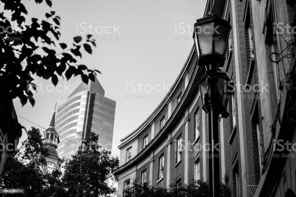 Contrast between an old and a modern building. Black and White photo stock photo