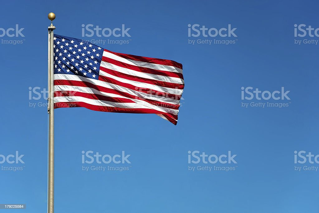 Contrast photo American flag waving against solid blue sky stock photo