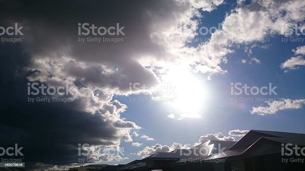 Contrast storm cloud meeting sunny sky. stock photo