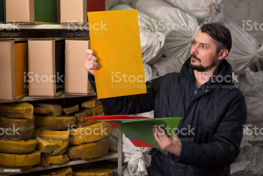 Factory man holding and examining yellow beeswax candle sheet.
