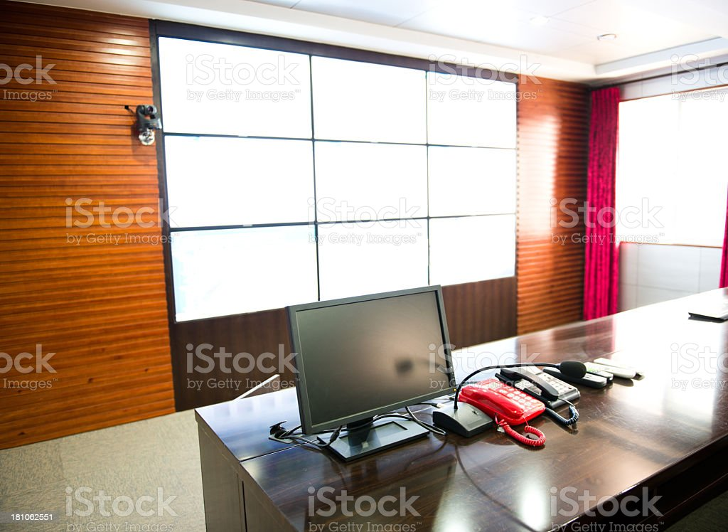 A control room with a screen and multiple table phones stock photo