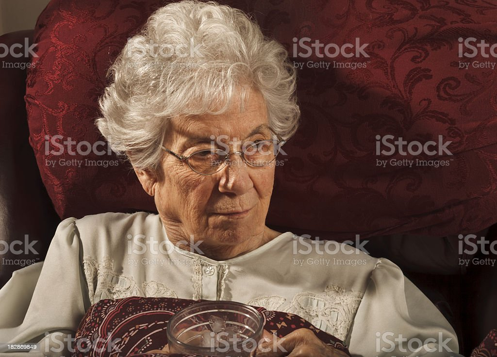 convalescing senior woman sitting in nightie holding glass stock photo