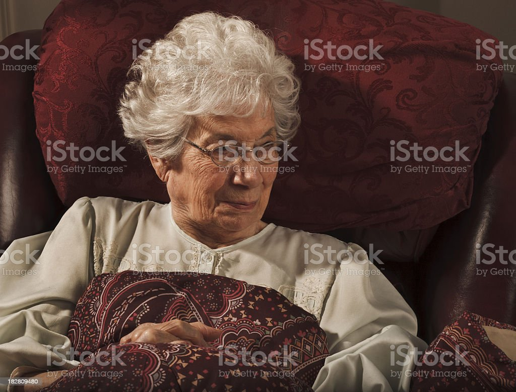 convalescing senior woman sitting in nightie with blanket stock photo
