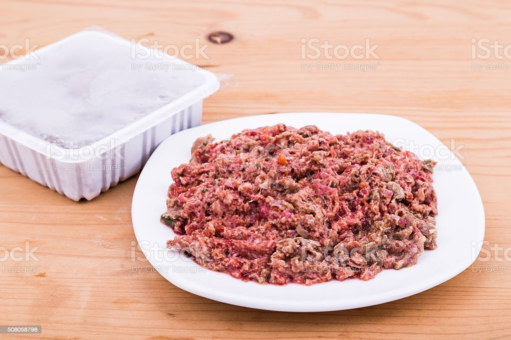Convenient packaged minced raw meat dog food on plate stock photo