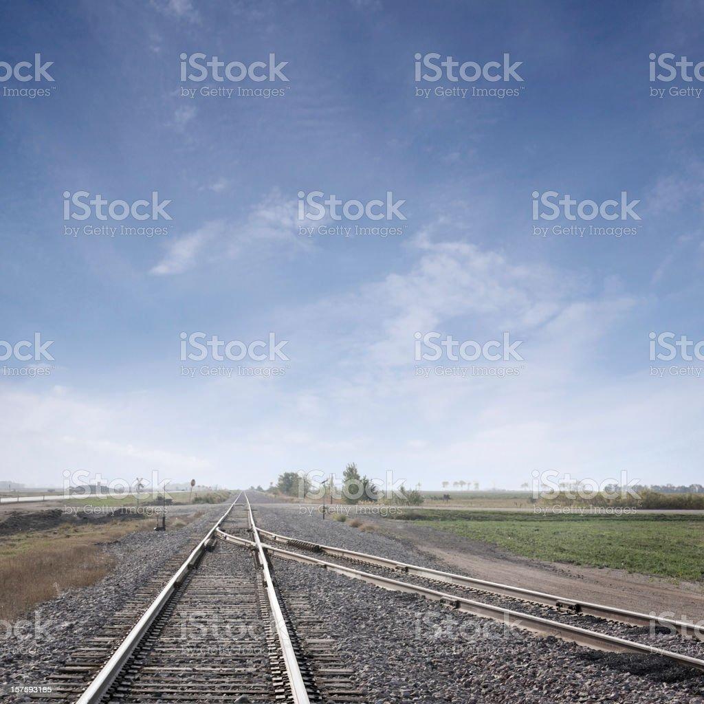 converging train tracks under big sky royalty-free stock photo