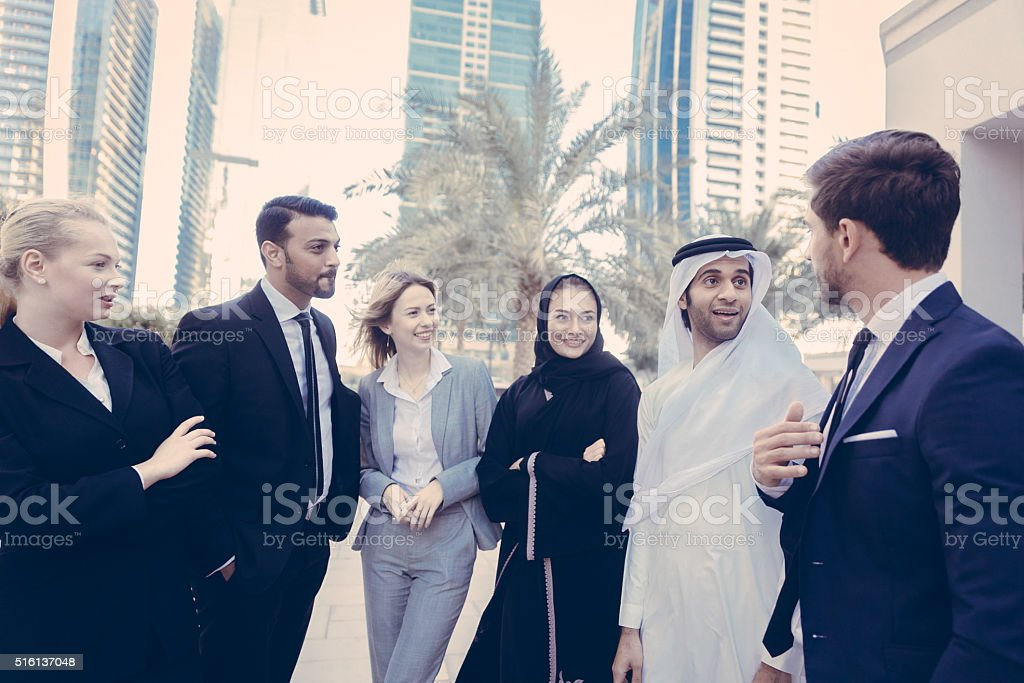 Conversation between multicultural business professional outside stock photo