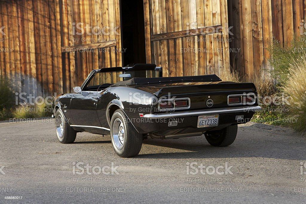 Convertible Camaro next to barn stock photo