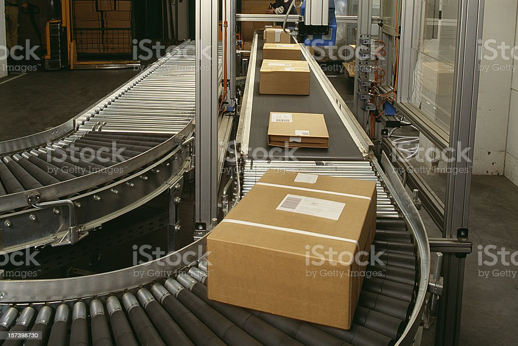 Conveyor belt curve showing brown packed postal boxes stock photo