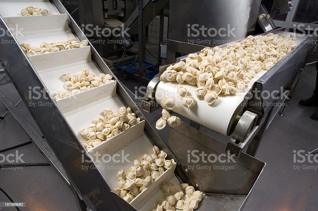 Conveyor belt dispensing tortellini  stock photo