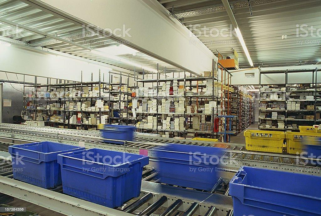 Conveyor belt warehouse storage distribution with blue plastic boxes stock photo