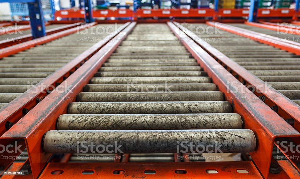 conveyor rollers in distribution warehouse stock photo