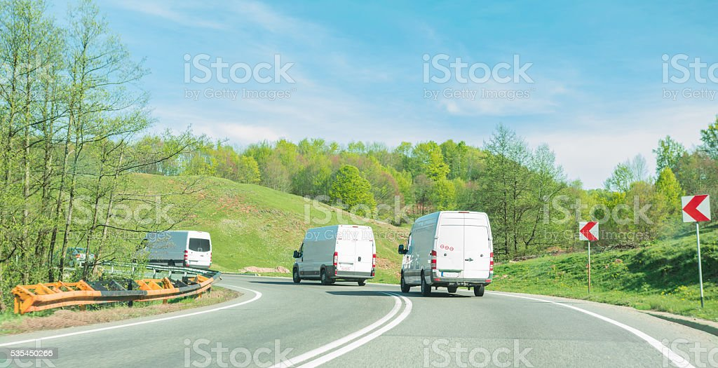 Convoy of white vans on the road stock photo